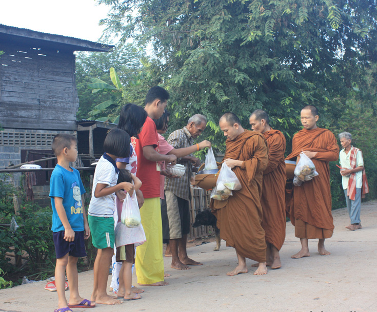 The monks walk barefoot around the neighbourhood   while the local people make merit by offering them food.