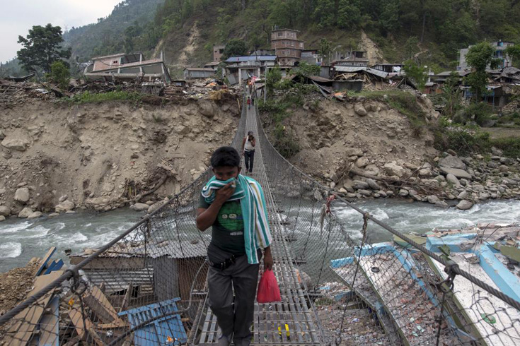 Local residents walk on a bridge, past collapsed buildings, after Tuesday's earthquake at Singati Village, in Dolakha, Nepal, May 15, 2015. REUTERS/Athit Perawongmetha