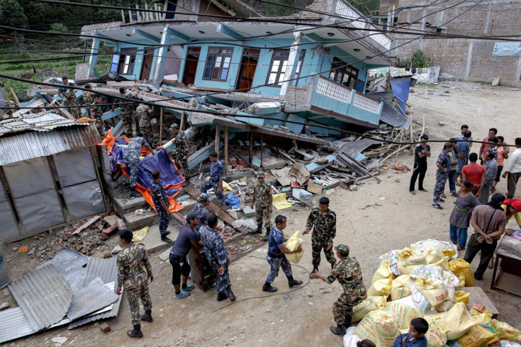 Nepalese military personnel try to salvage supplies among the debris at Arugat village in Gorkha, Nepal.