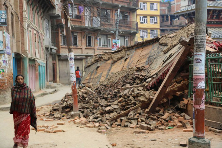 A woman walks by buildings destroyed by the earthquake in Nepal.