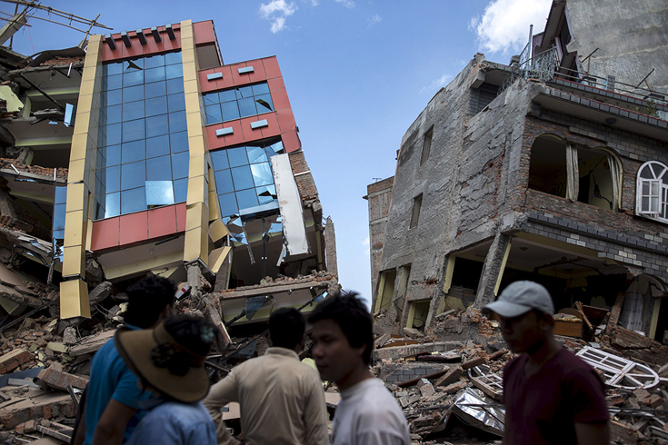 People walk past buildings in Kathmandu after a second major earthquake struck(Athit Perawongmetha/Reuters)