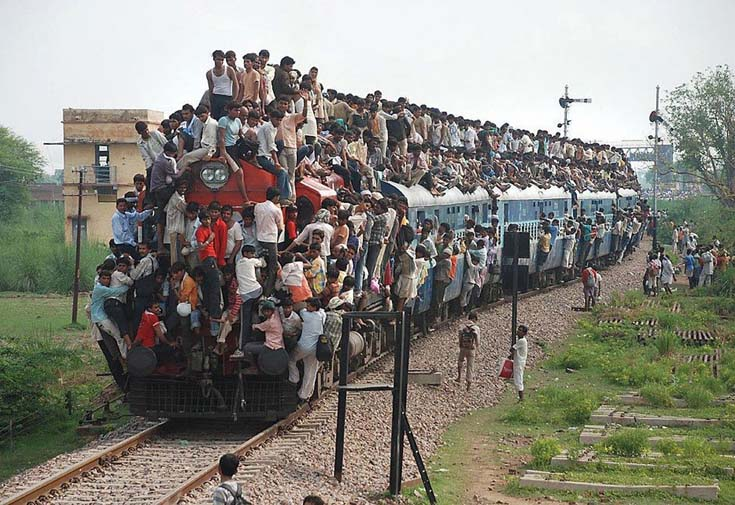 Indian commuters hang off   a train in India