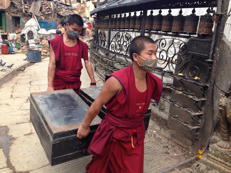 Young monks retrieve items and pitch in with the clearing up of rubble. (Photo: Anand Krishna)
